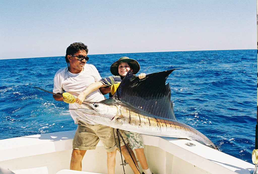 Max from childhood catching a marlin with help